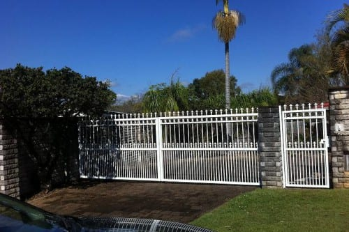 Automatic white metal gates built outside the house