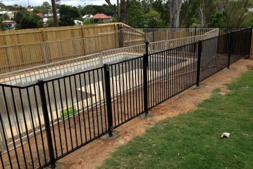 Construction of swimming pool surrounded with black metal fences